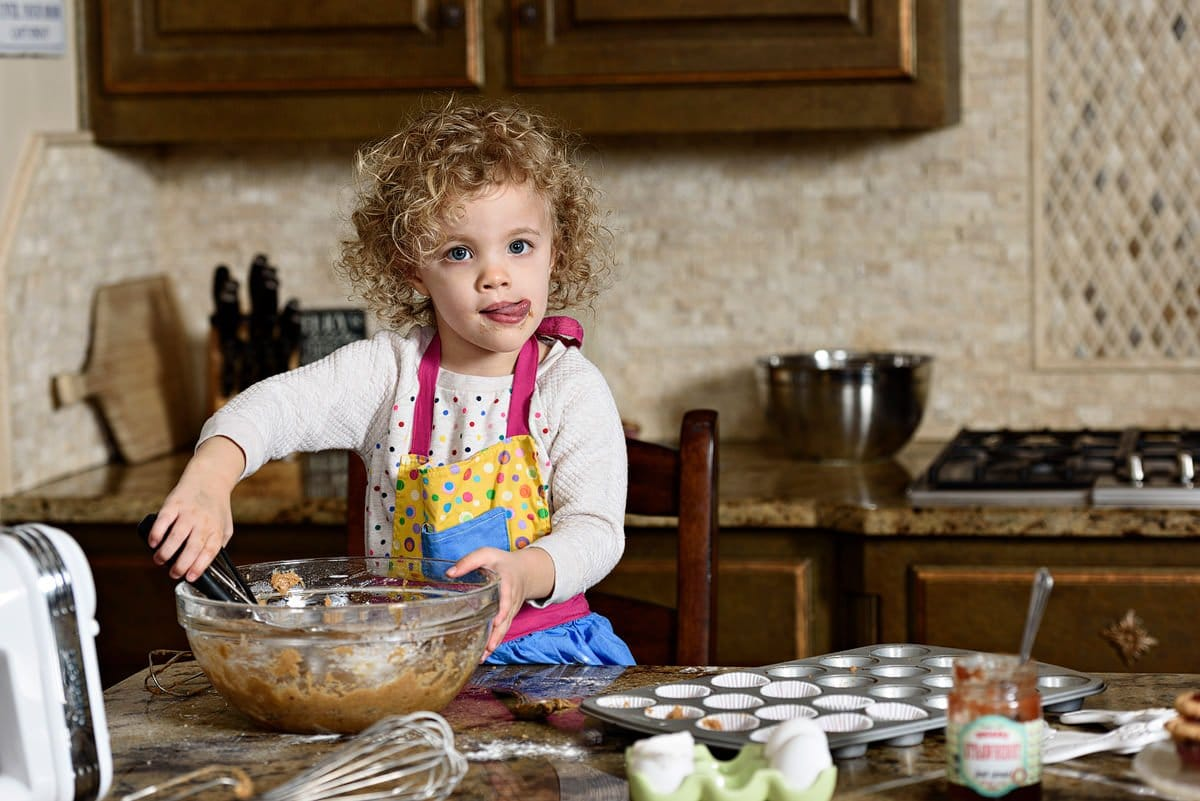 frisco family photographer 3 year old bakes with mom in kitchen