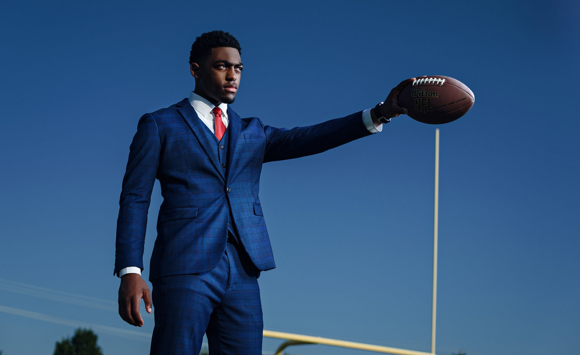Dallas senior portrait of athlete from McKinney North Football in blue suit holding football