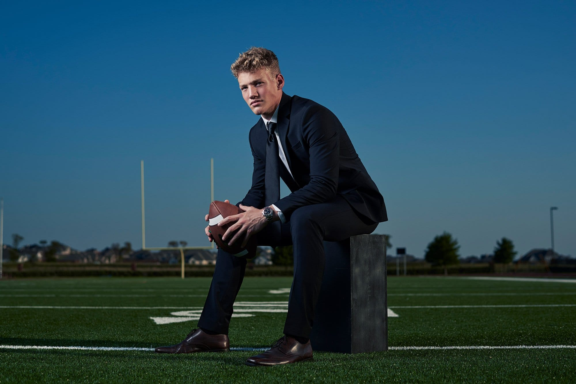 Prosper senior photos of football player on high school field in suit