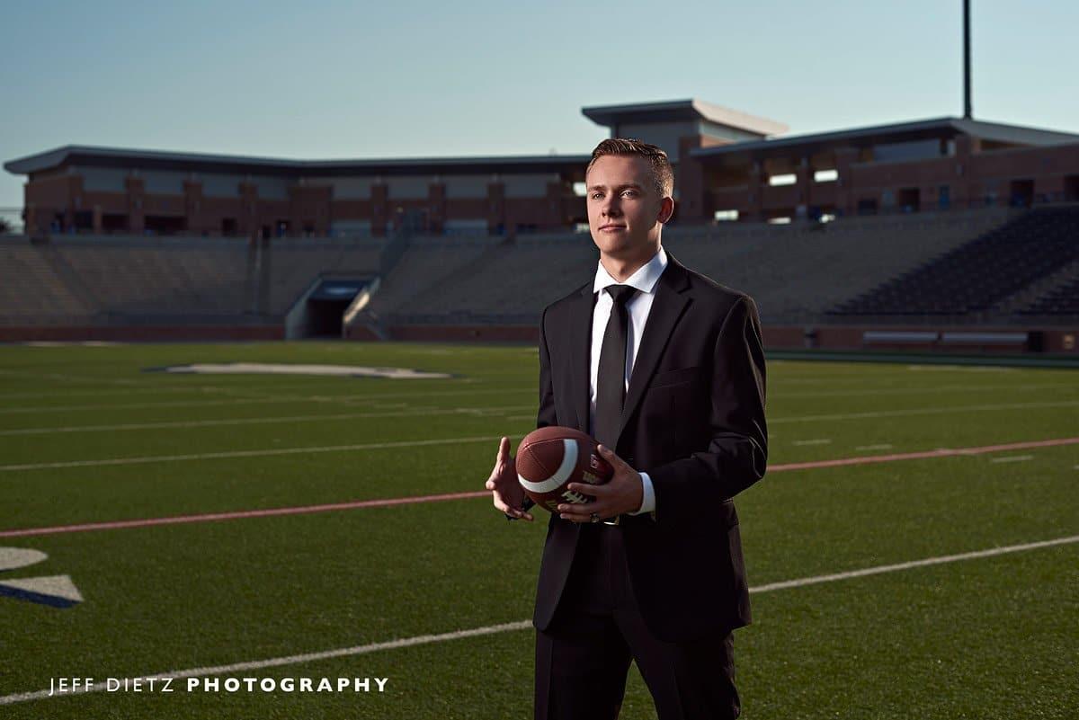 allen senior photos of football player in suit at eagles stadium