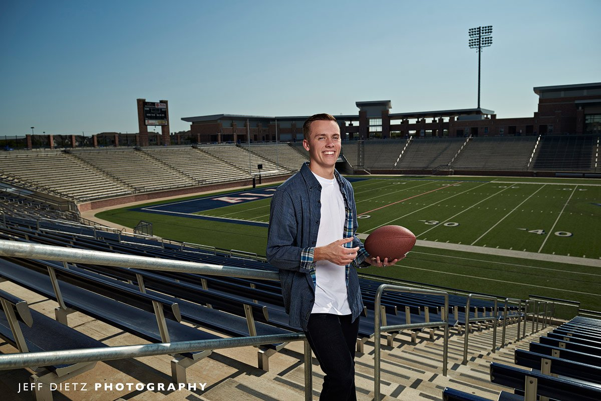 senior portraits allen student with football in the stands of eagles stadium