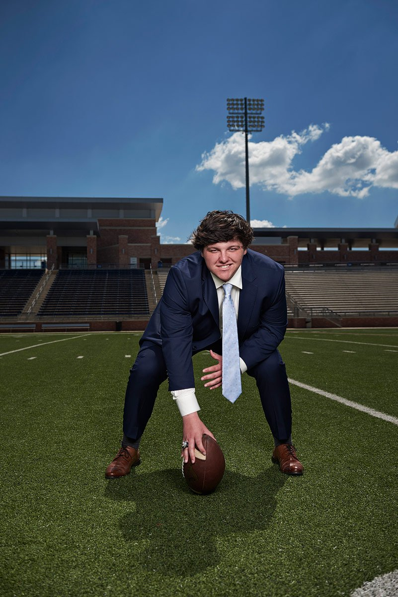 allen eagles football starting center in a blue suit gets ready to hike the ball