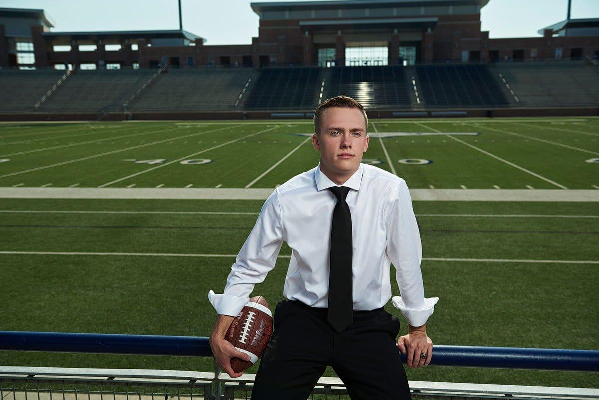 Allen defense poses in suit for senior photos in eagles stadium