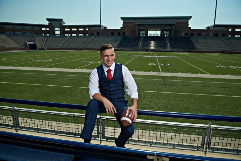 allen senior pictures of football player with eagles stadium behind him
