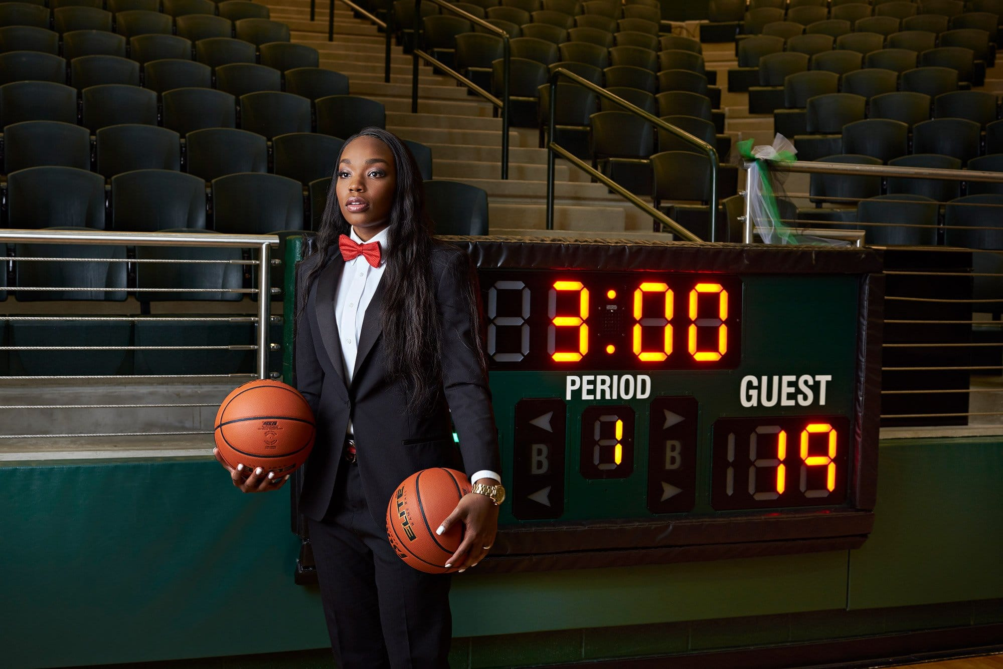 Jordyn Oliver stands by the scoreboard for senior portraits at the Prosper high school arena