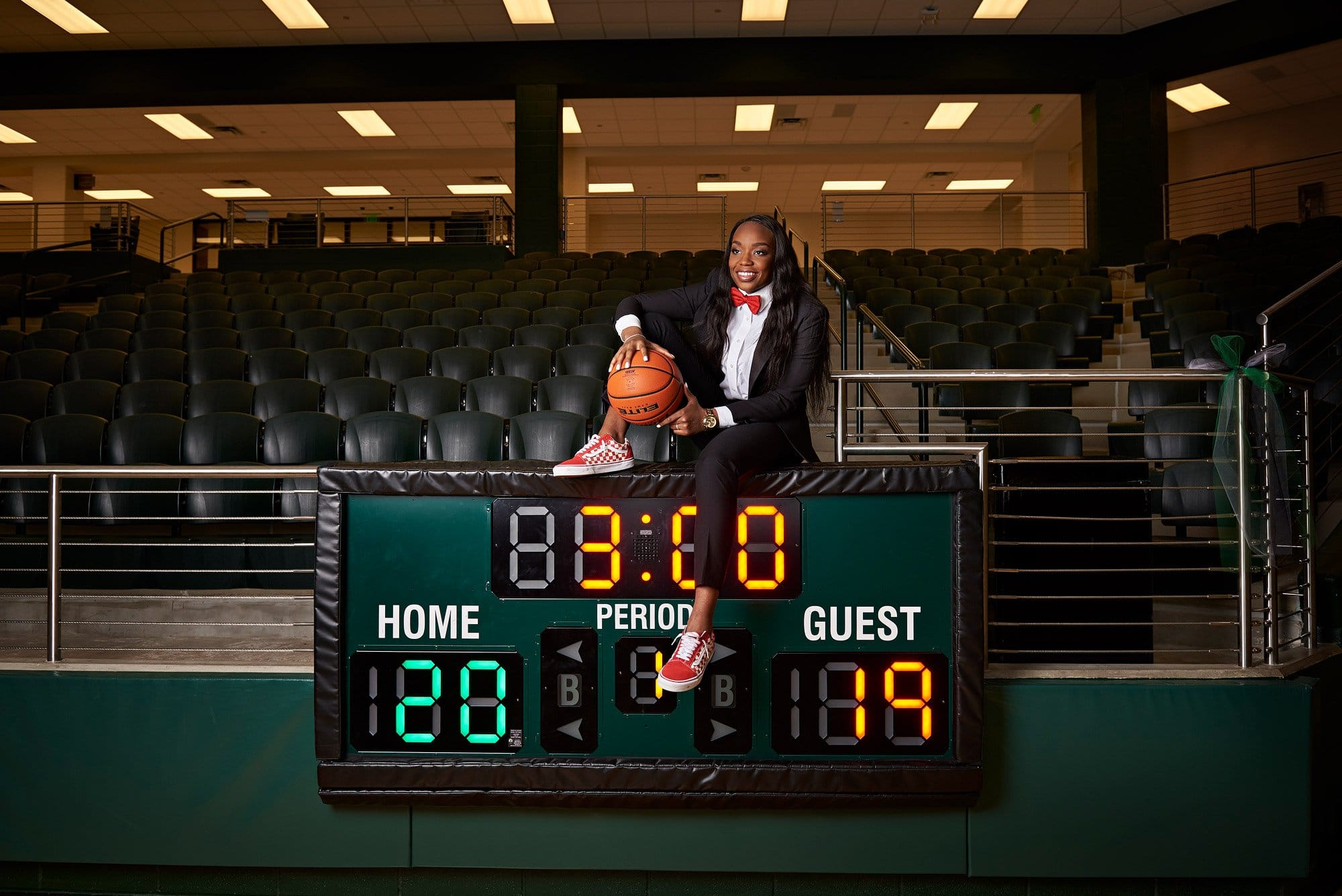Jordyn sits on the scoreboard at the prosper basketball court for her senior photos with photographer jeff dietz