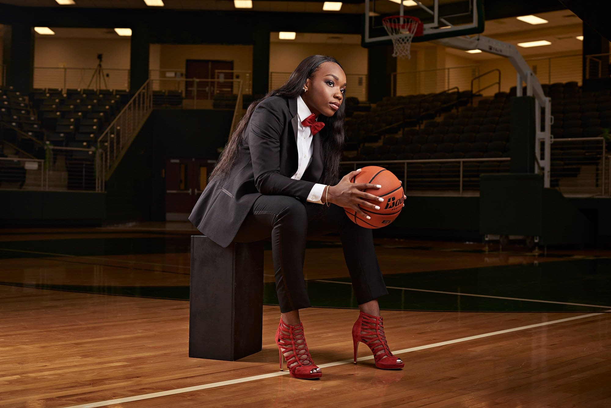 Prosper Girls senior basketball player Jordyn on basketball court in tuxedo at prosper high school