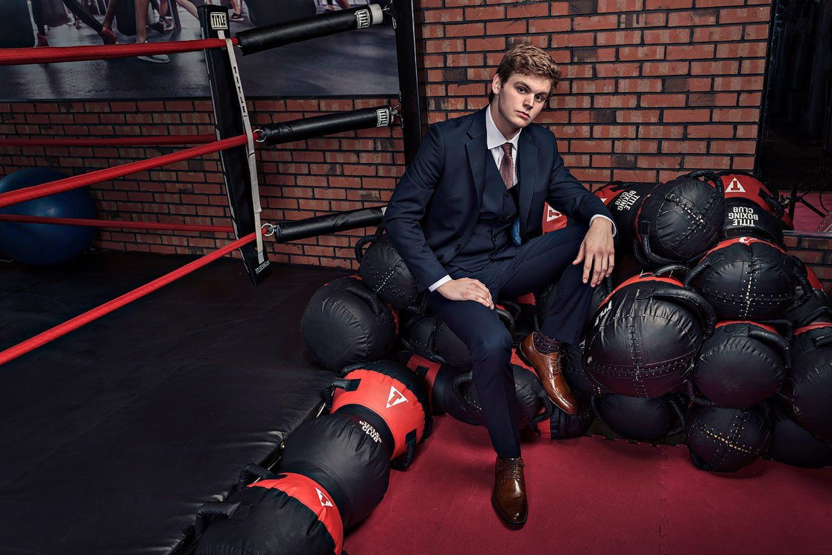 plano senior portraits in the gym with MMA workout bags in suit
