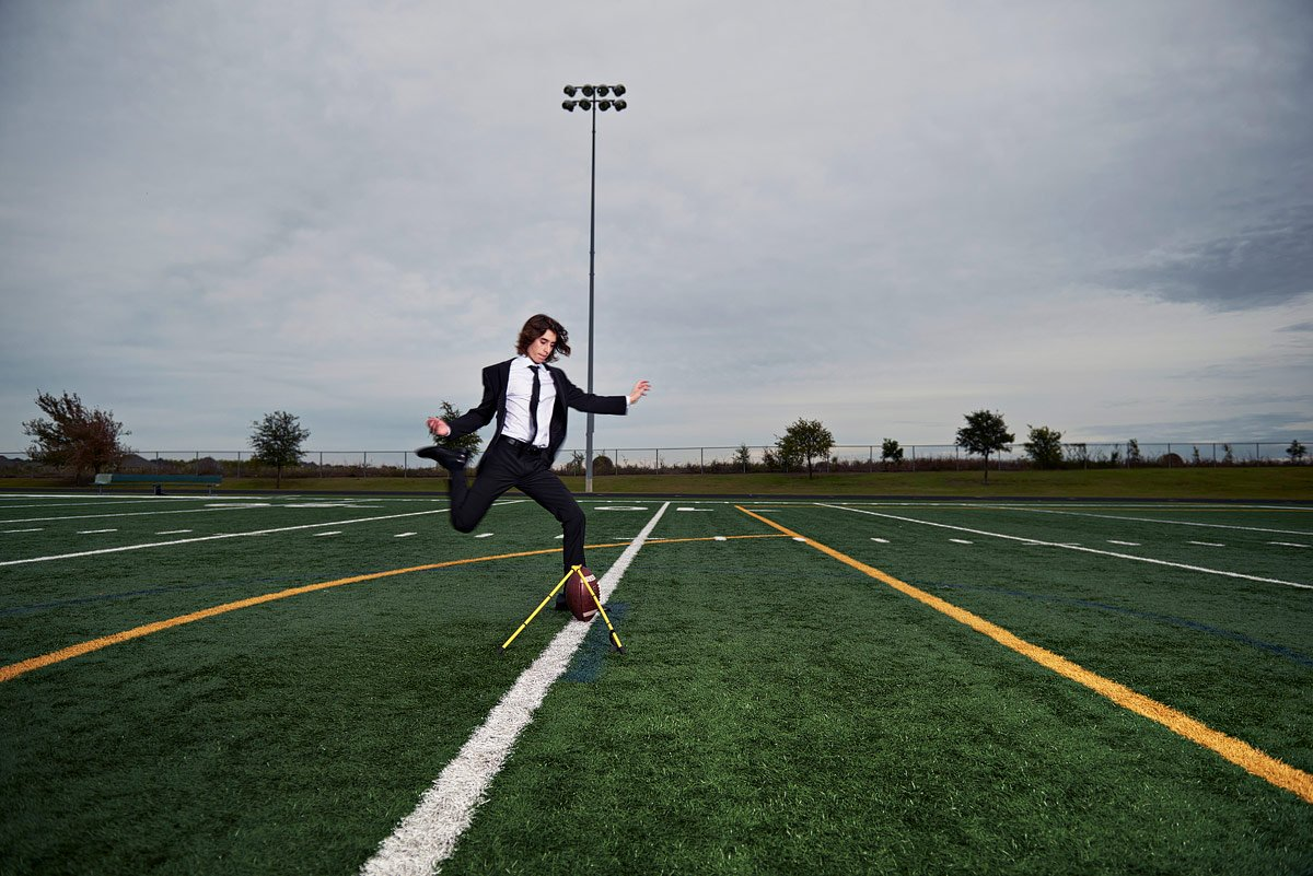 prosper football player kicking field goal in suit with senior photographer Jeff Dietz