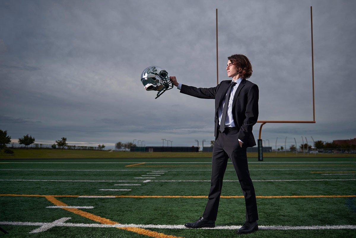 Prosper Football kicker senior photos in suit with silver helmet