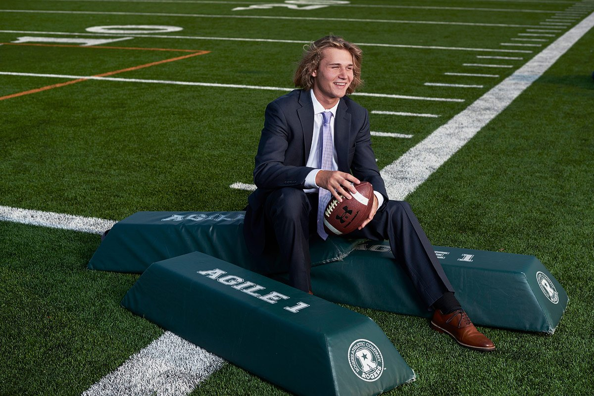 senior pictures prosper tx football player in suit at prosper high practice field