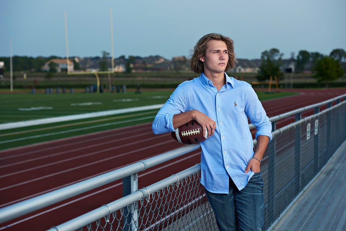 senior pictures with football at field prosper texas