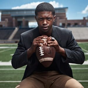 allen athlete crushes football in senior pictures in sports jacket