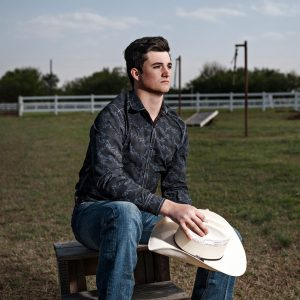 prosper senior guy photos with cowboy hat sitting at horse farm