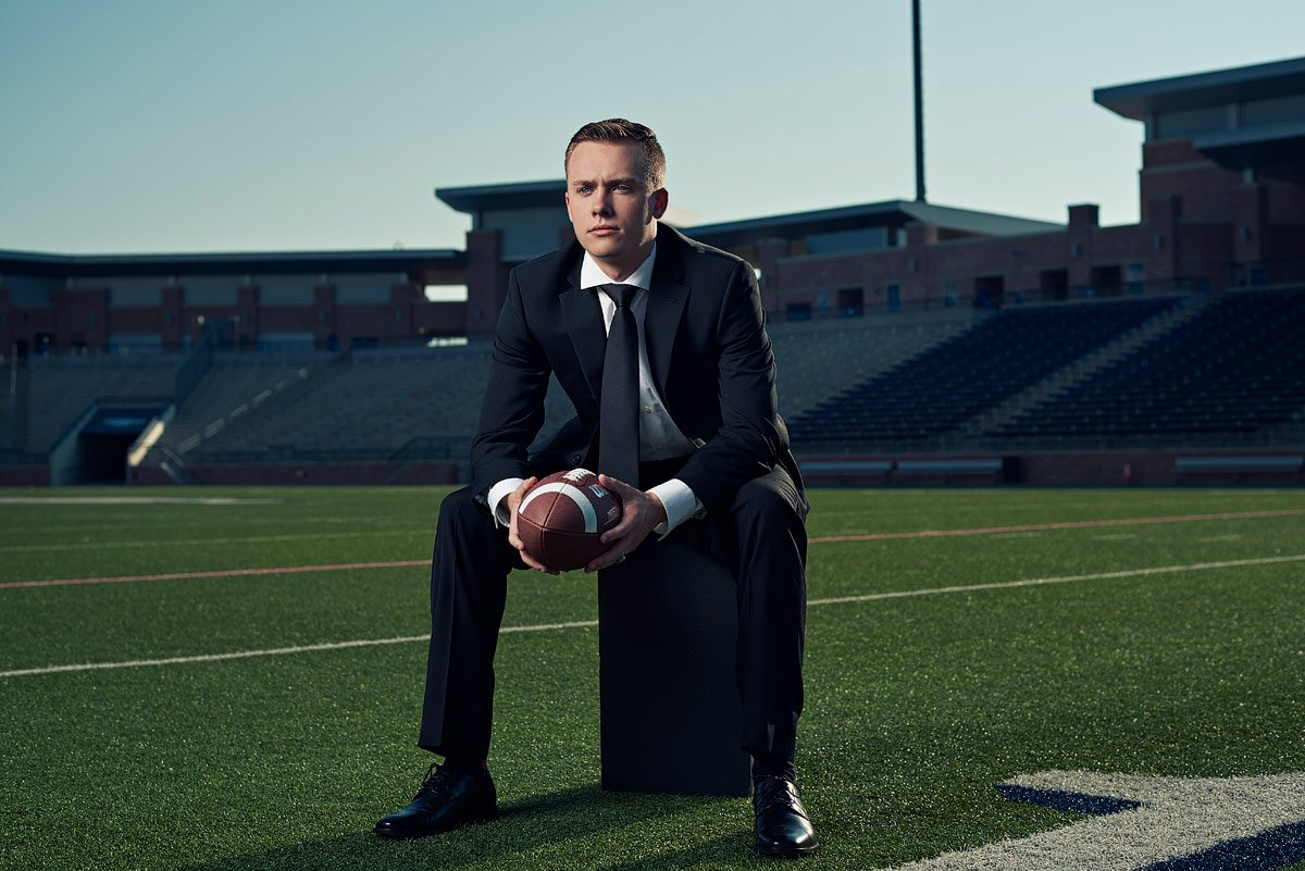 senior student on the allen football field for senior photos in a suit