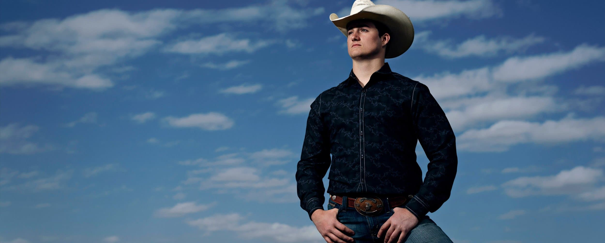 dallas boys senior pictures in cowboy hat with blue skies by mckinney photographer