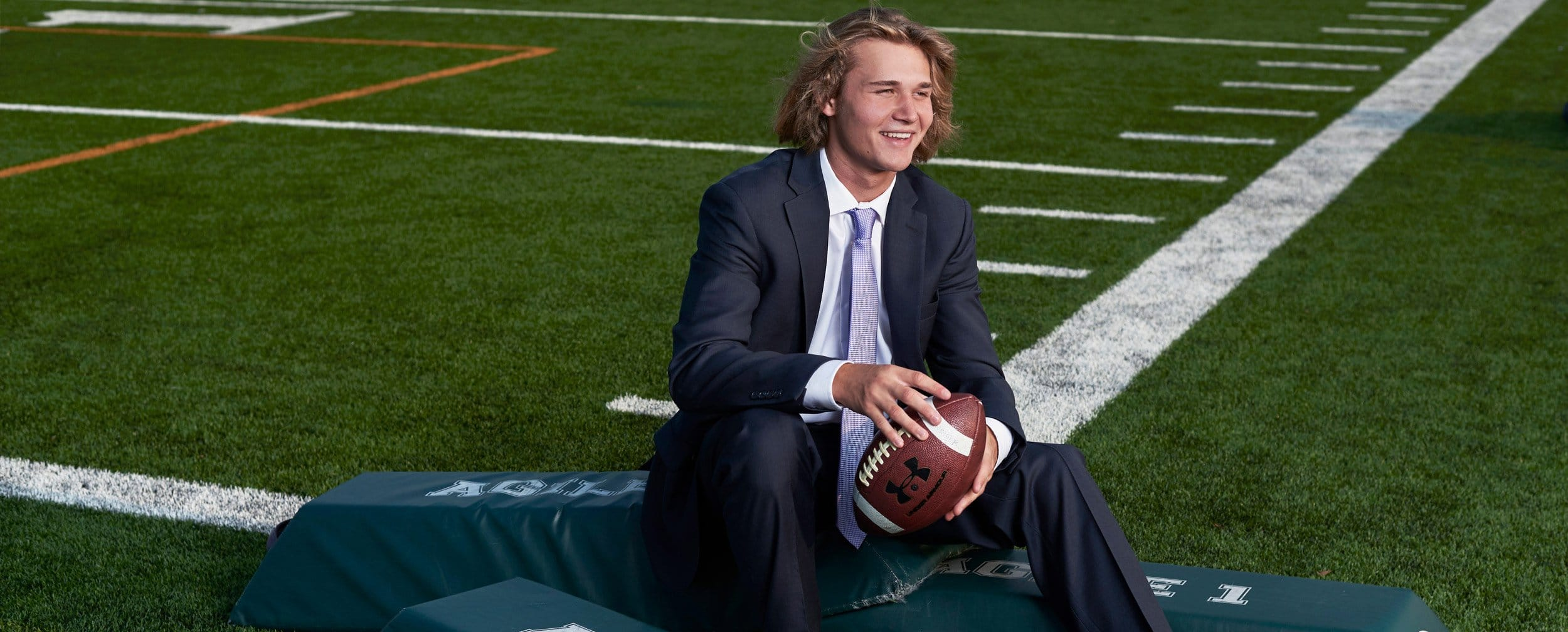Dallas High School sports portraits of football player from prosper on field in suit