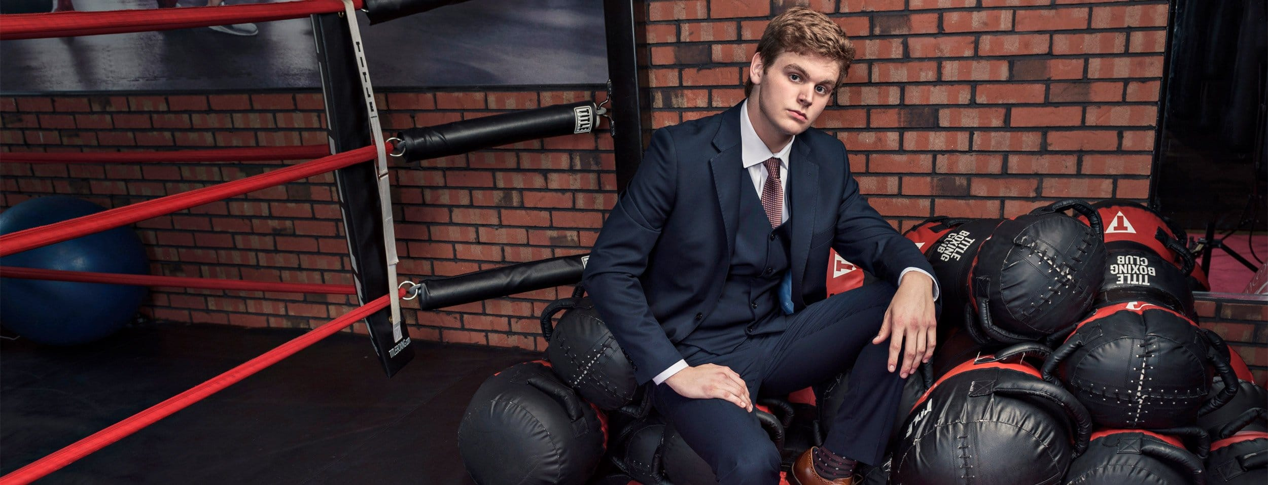 Dallas portrait photographer of boy plano high senior at boxing gym in Mckinney in a suit