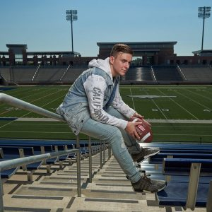 allen senior takes photos at the football stadium in a hoody in the bleachers