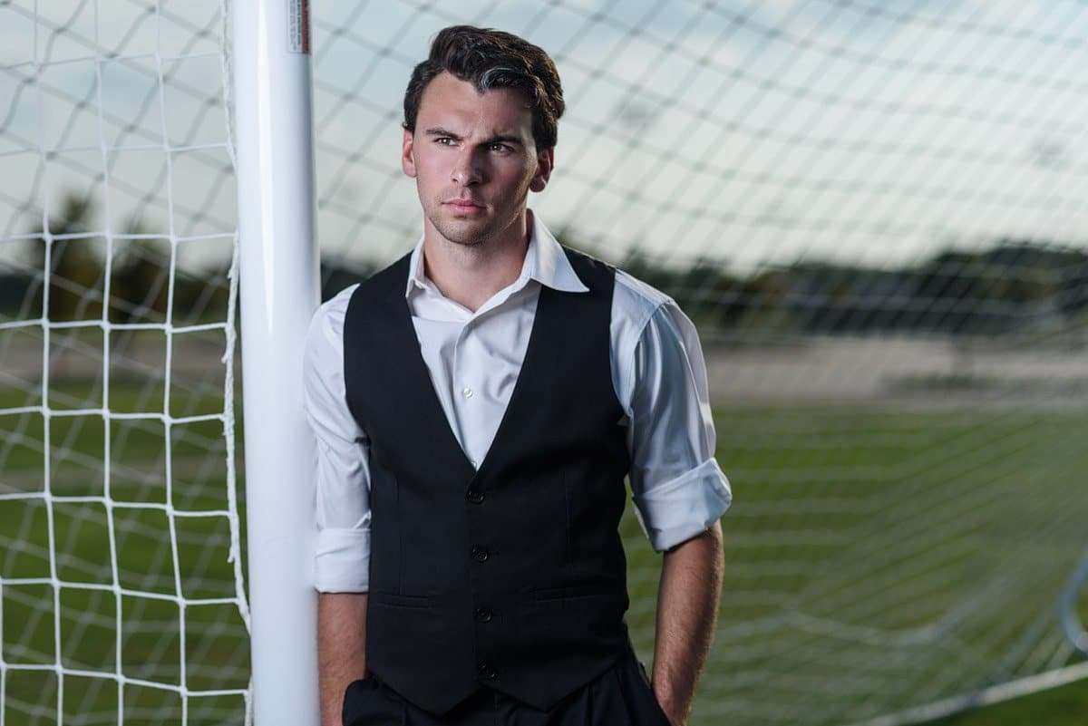 photos of soccer player by a goal in a vest for senior portraits