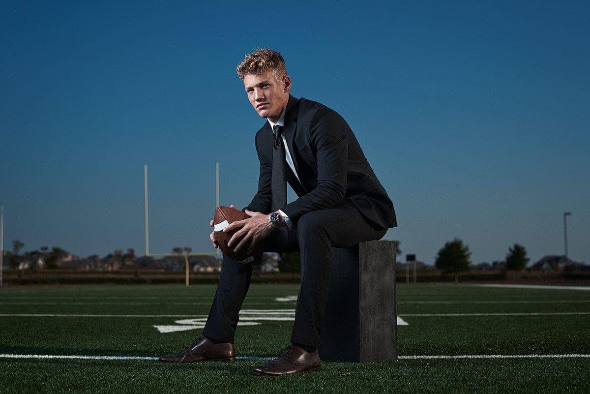 prosper senior football player sitting on field for senior photos