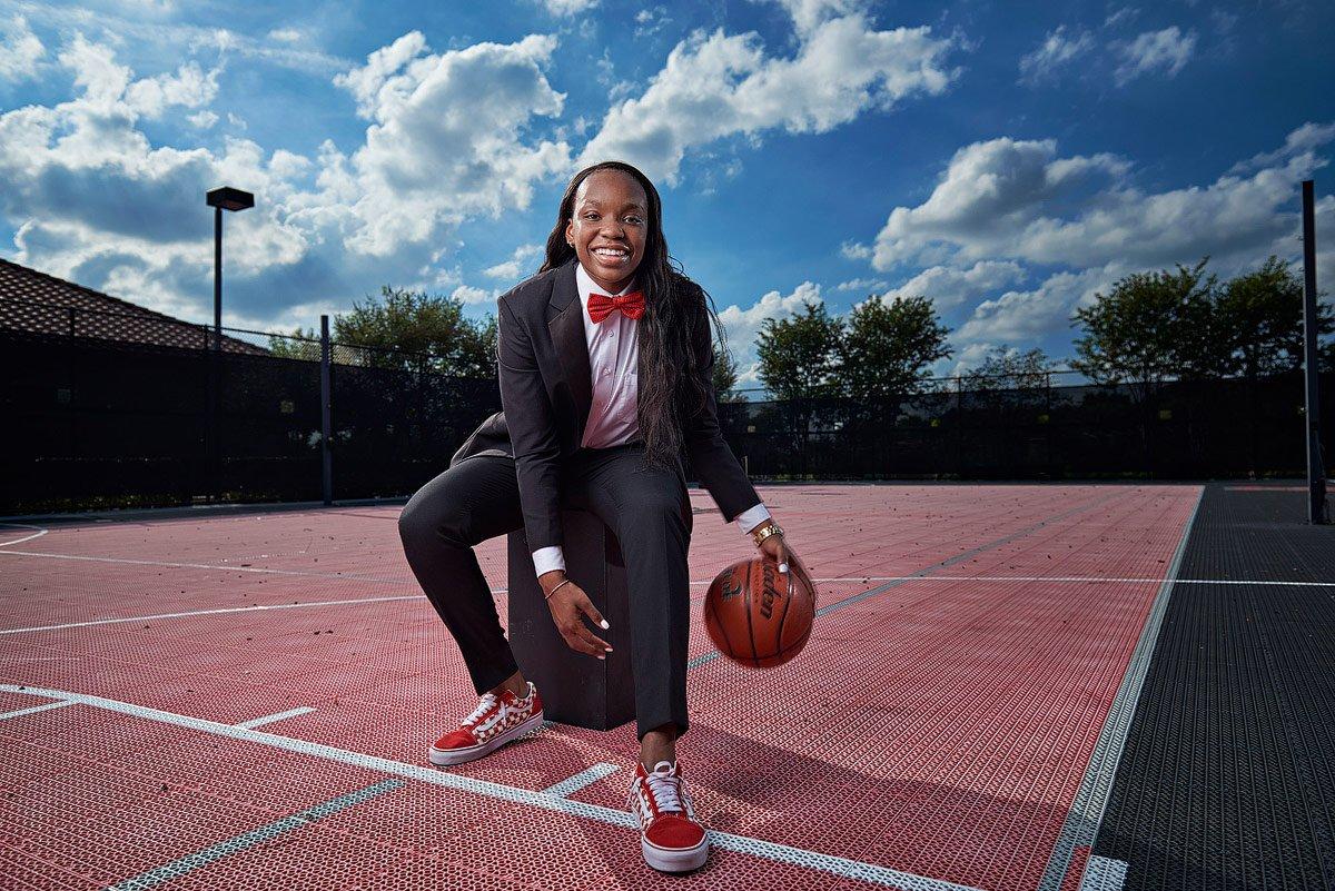 Jordyn Oliver dribbling between her legs in a suit on outdoor basketball court in prosper tx