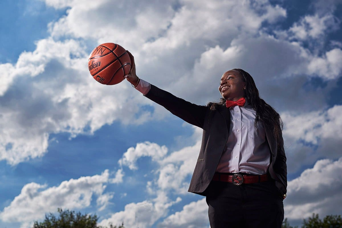prosper girls basketball player palms ball in hand wearing a suit in front of clouds