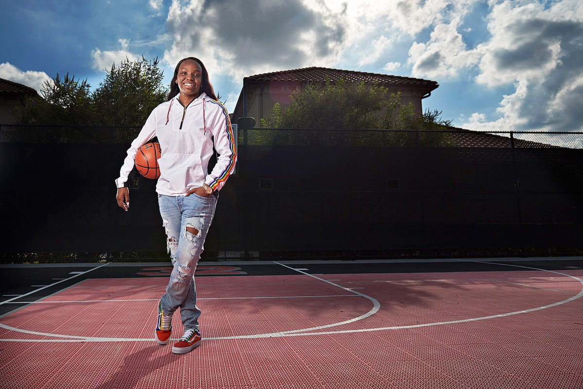 prosper girls basketball player for senior portraits on outdoor court holds ball in arms