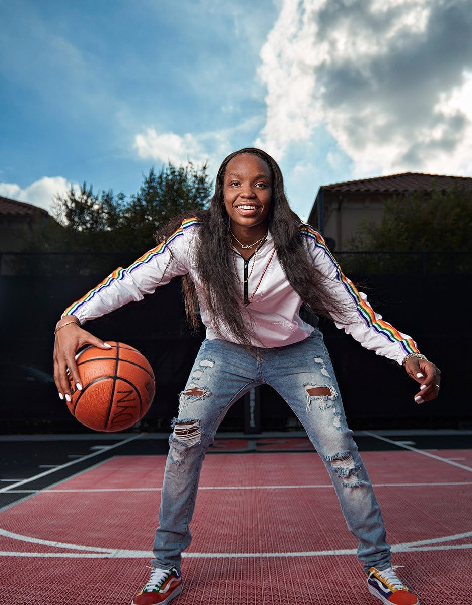 dallas high school basketball player dribbles in white jacket and jeans for senior pictures