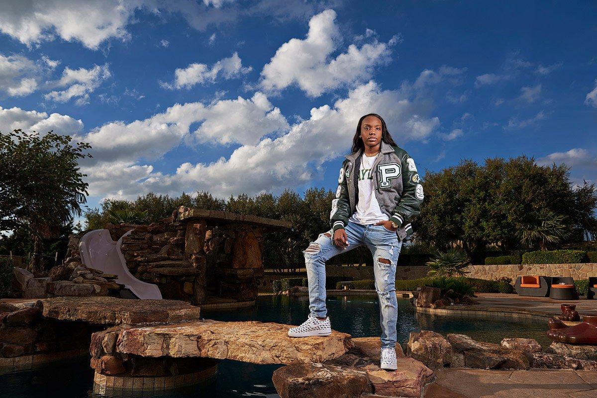 Jordyn Oliver stands on rocks over a pool at home in prosper for senior pictures