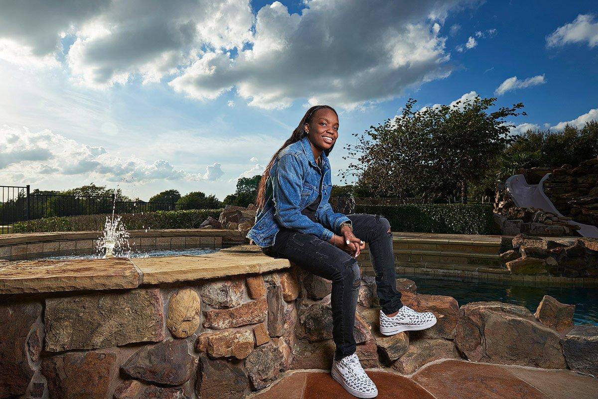prosper senior sitting on edge of fountain for senior photos jean jacket and black pants