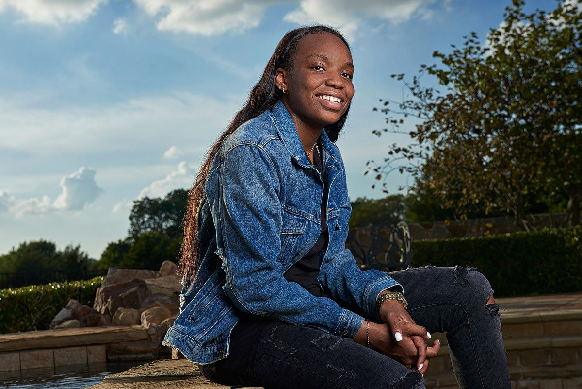 teen girl in jean jacket sits on rock wall for senior photos