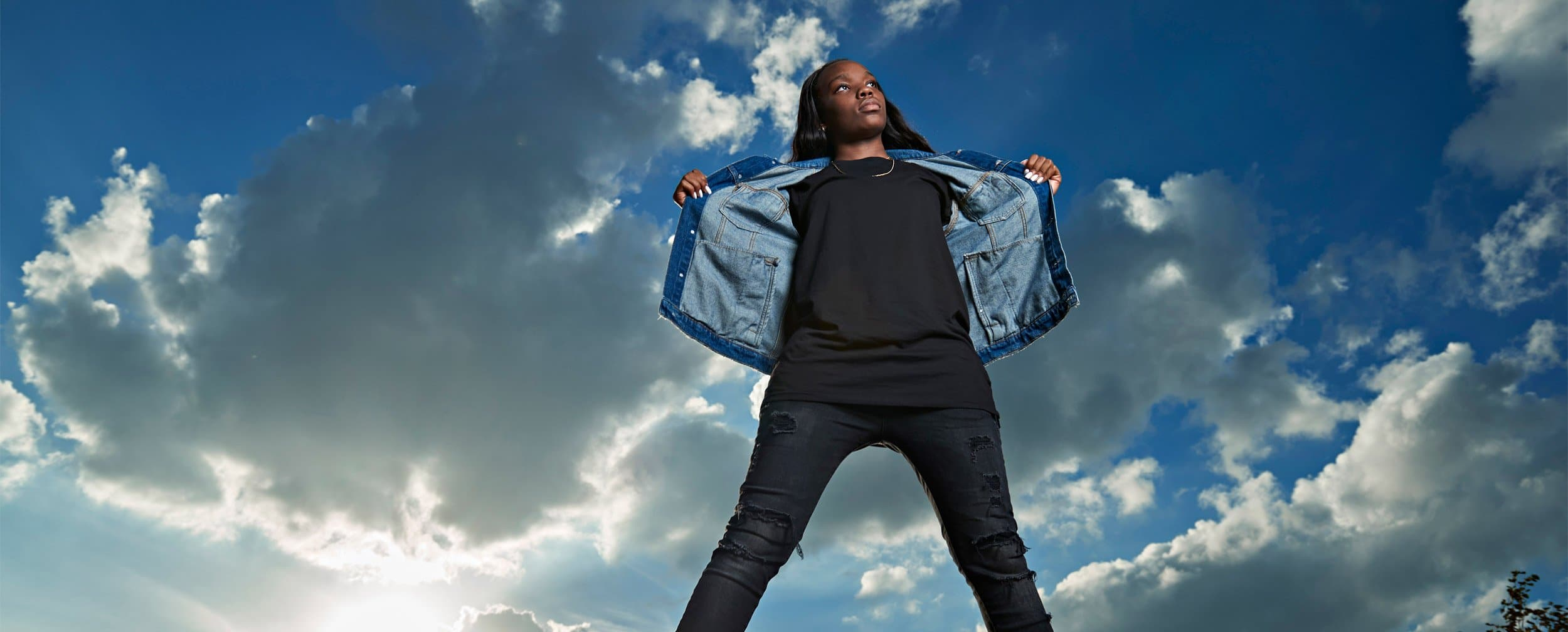 prosper girls basketball player Oliver wears a jean jacket for senior pictures with blue sky