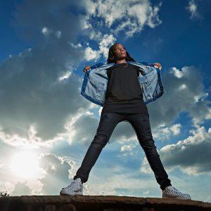 prosper girls senior stands on rock with jean jacket