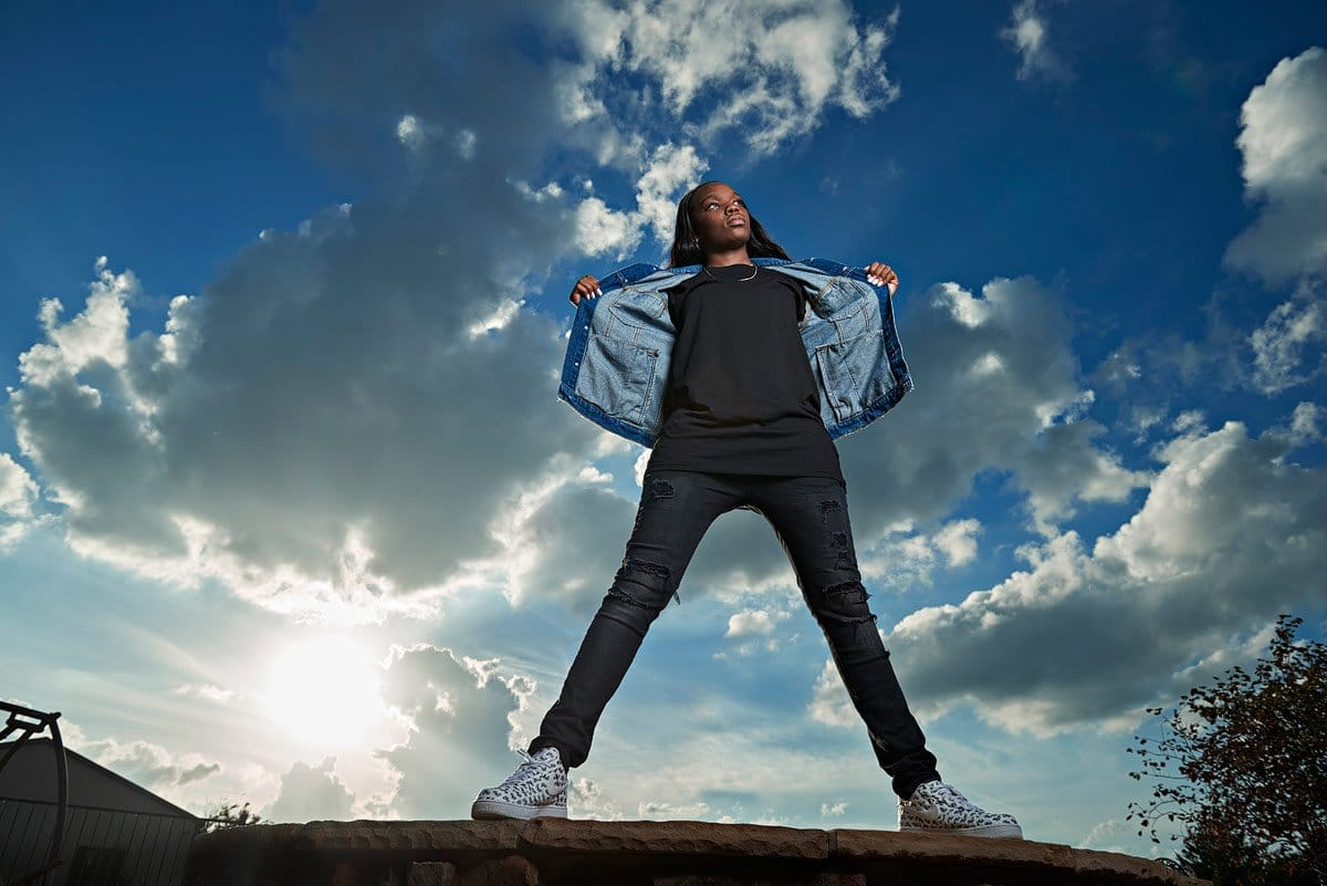prosper girls senior stands on rock with jean jacket