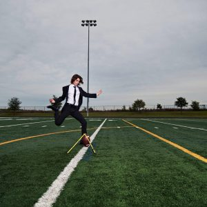 prosper kicker kicking field goal for senior portraits in suit