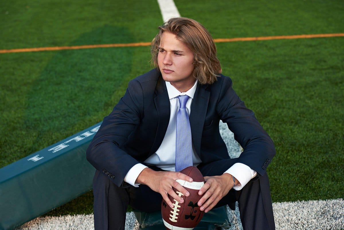 prosper senior sitting on football practice field in suit for senior portraits