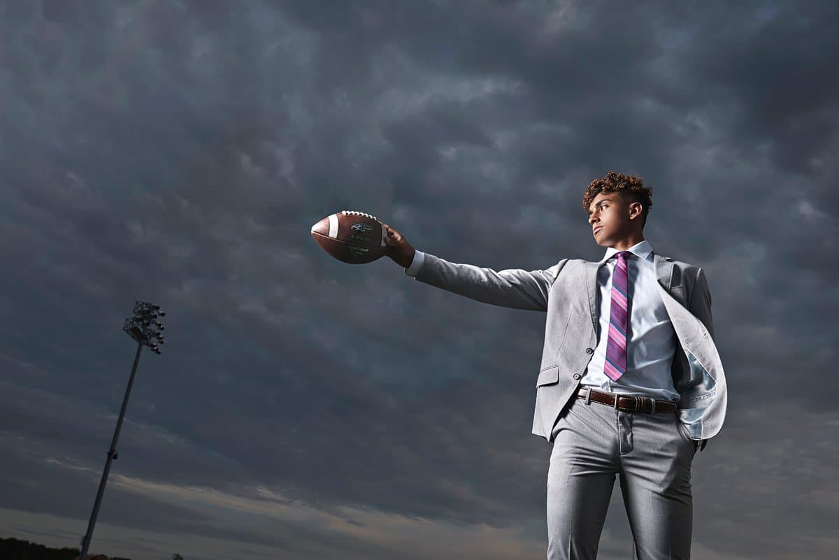 high school senior holding football stretched out in front of clouds