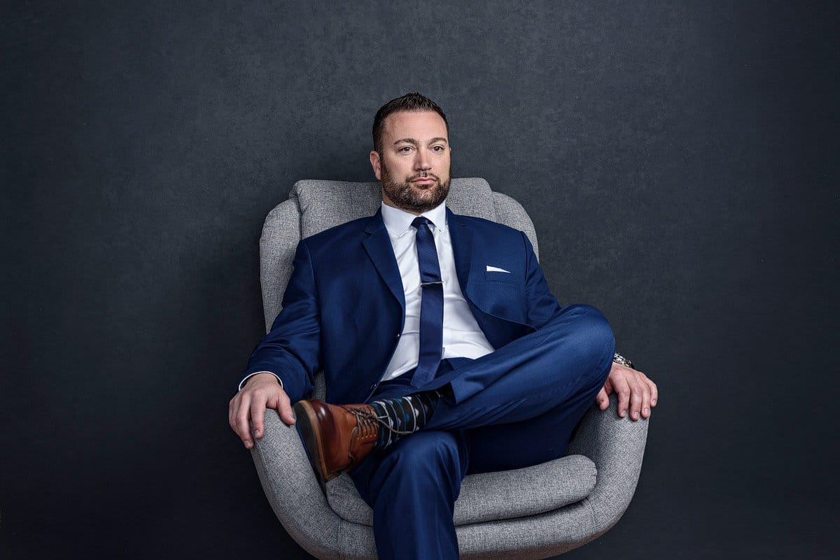dallas lawyer headshots in a blue suit legs crossed in gray chair frisco texas