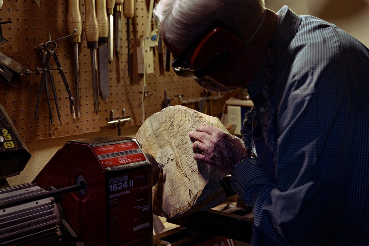 world war 2 veteran in mckinney texas photographed working on a block of wood in woodshop