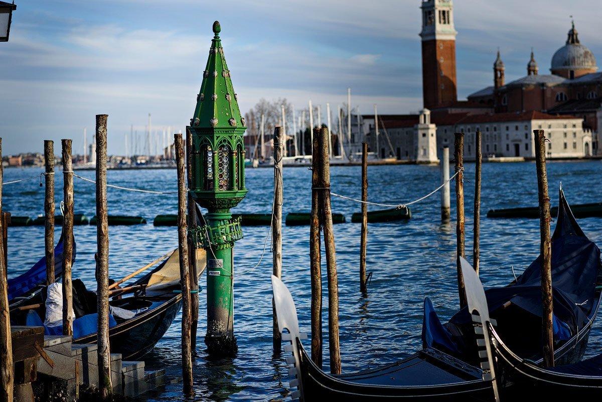 Green lantern in water next to gondolas overlooking st giorgio island in italy