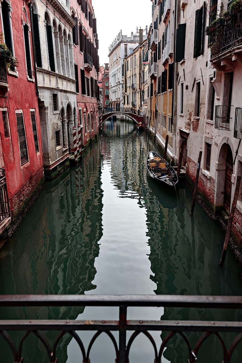 canal with colorful homes in venice italy from bridge