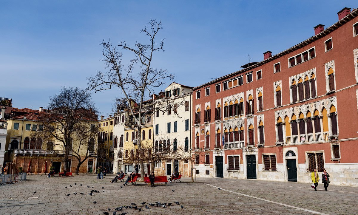 piazza in venice italy with red benches and buildings