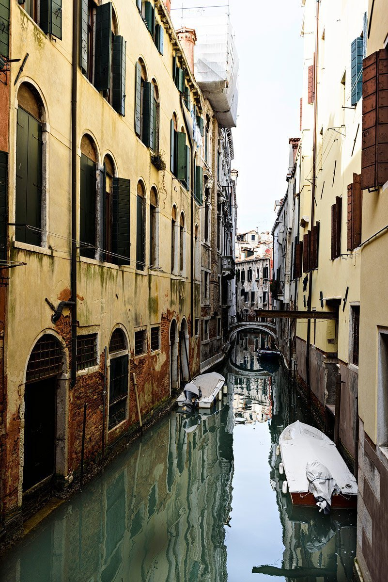 canal in venice italy with yellow painted buildings and speed boats