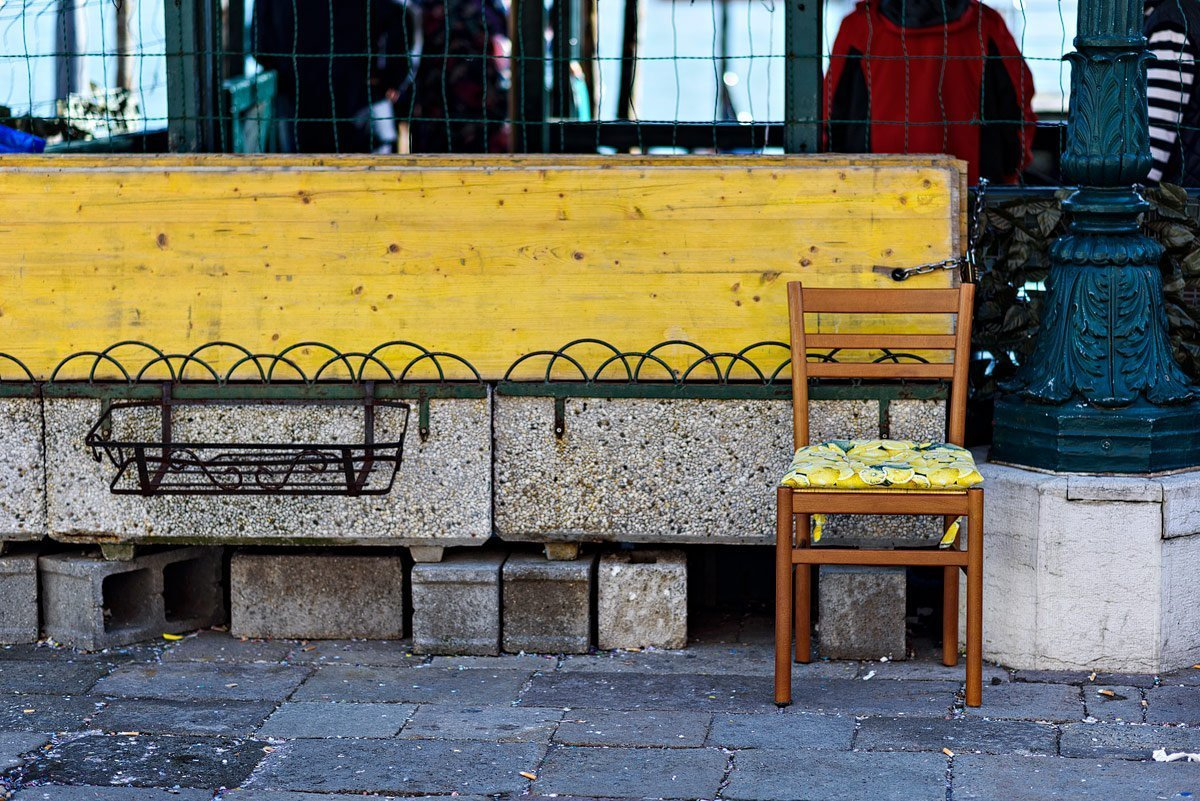 yellow wooden chair on the street in venice italy