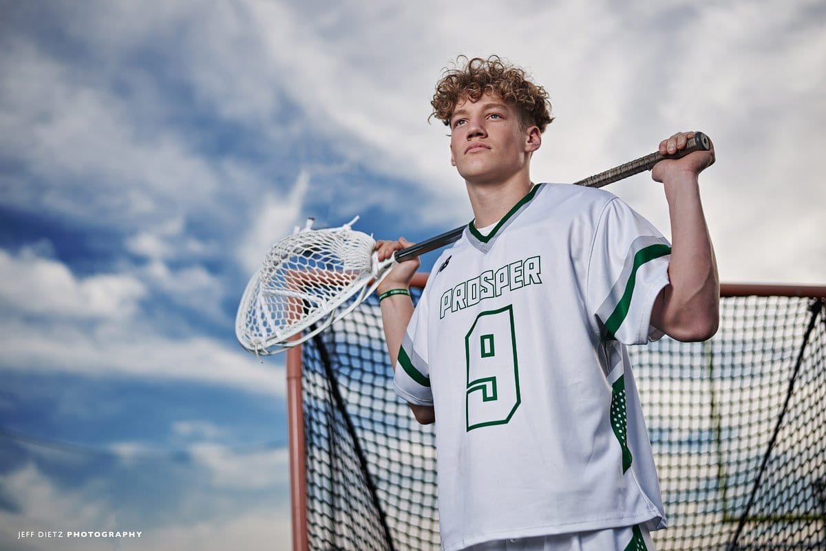 prosper lacrosse goalie poses with stick and blue skies by the net senior portraits