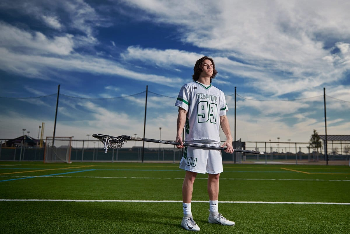 prosper lacrosse player stands with his defensive stick in jersey at frontier park