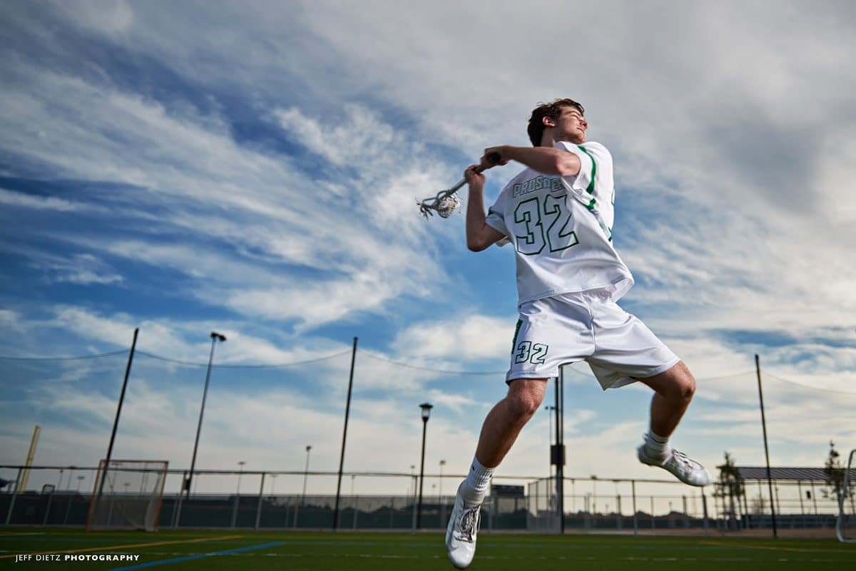 Prosper offensive lacrosse player jumping for team photo