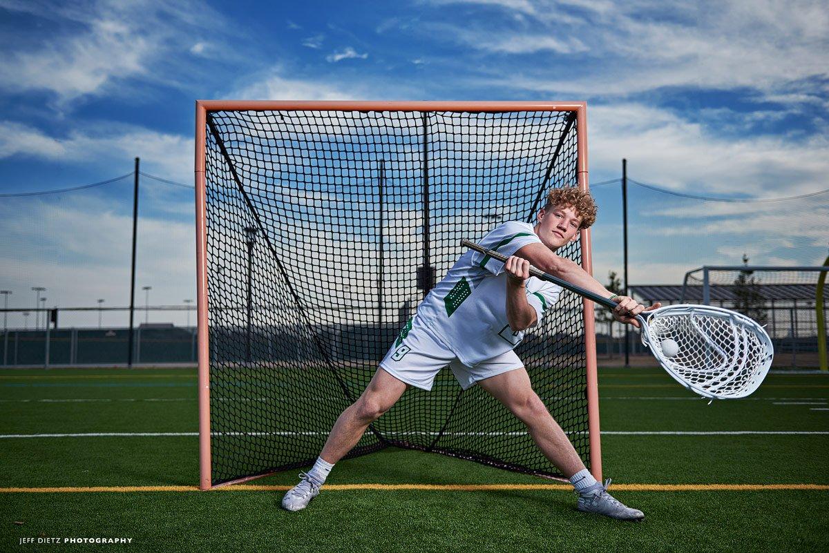 prosper lacrosse goalie blocks a shot in senior portraits at high school