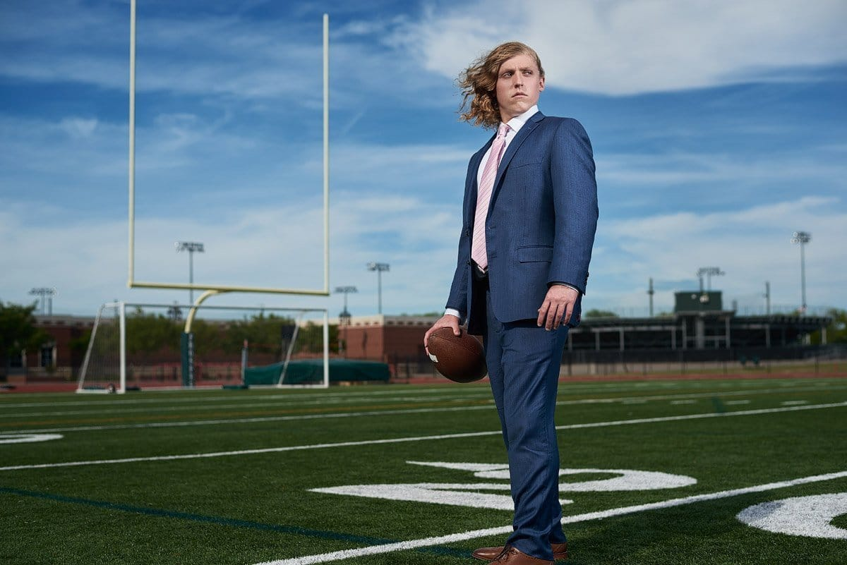 prosper senior football player in a suit on the field at the high school